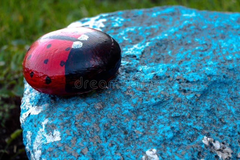 Insekt dzwoniłem ladybird robią ich malujący atramenty i kamień Postać stojaki w ogródzie na błękitnym kamieniu zdjęcie stock