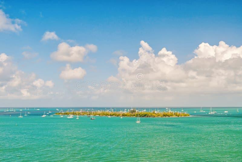Inselland und -Segelboote im Türkismeer in Key West, USA Meerblick mit Segelbooten auf bewölktem blauem Himmel Segeln und stockbild
