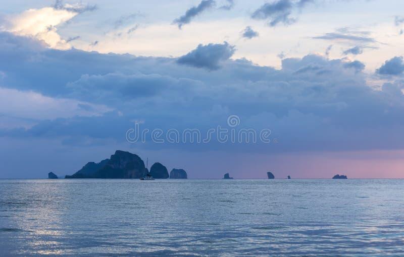 Inseln auf Seehorizont und drastischen Wolken auf Himmel nach Sonnenuntergang in der Dämmerung stockbild
