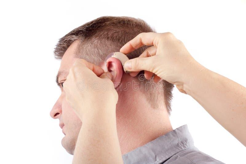Inserción del audífono foto de archivo