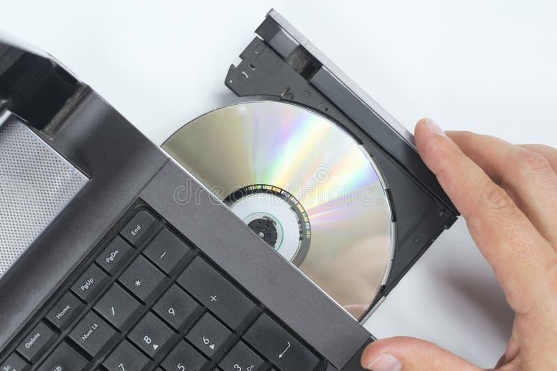 Inserisca il disco nel computer portatile immagini stock