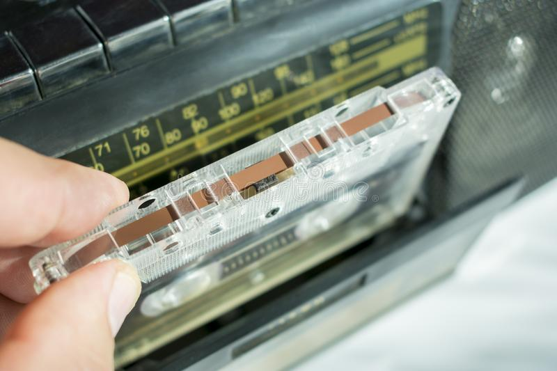 Inserisca un'audio cassetta in un registratore fotografie stock