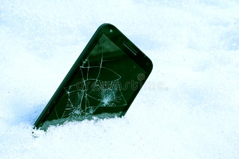 Inserted into the snow unnecessary smartphone with a broken screen, blue tinted picture. Cell phone thrown in the snow in the winter stock images