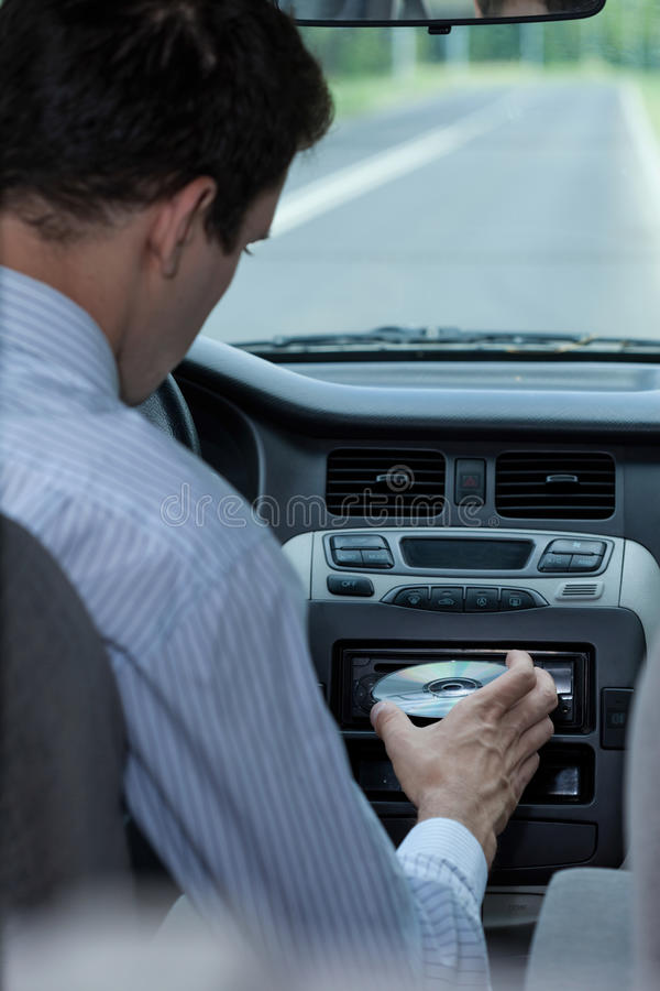Inserting CD in the car stock photo