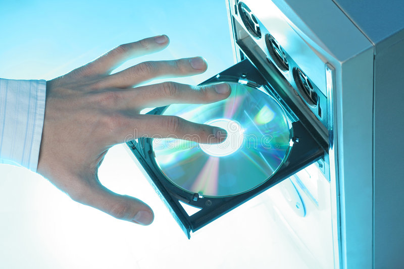 Inserting a CD-ROM. Into a personal computer stock photos
