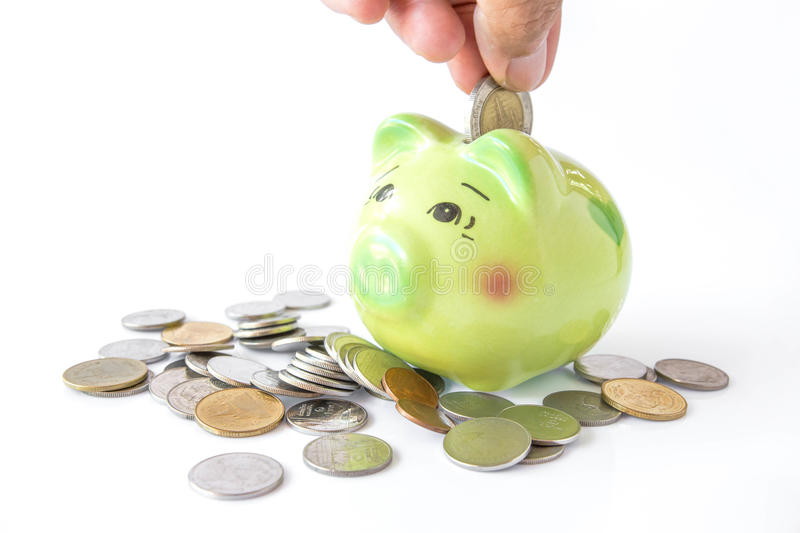 Inserting a coin into a piggy bank.  stock photo