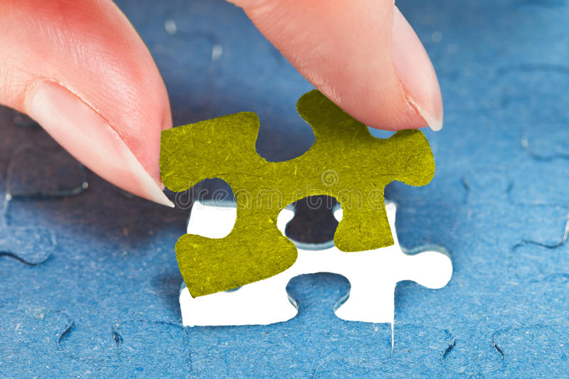 Inserting the last piece of puzzle stock photography