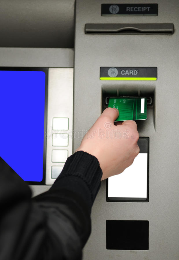 Inserting plastic card visa into ATM. Cash withdrawal. Woman's hand inserting plastic card Visa into the ATM stock image