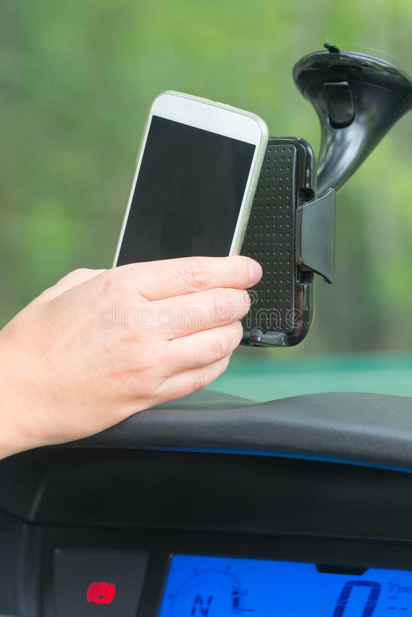 Inserting smart phone into the car holder. Hand inserting smart phone into the car holder and adjusting clamps royalty free stock images