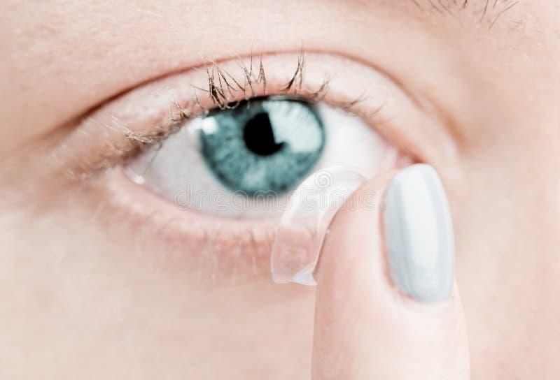 Insertion d'un verre de contact dans l'oeil femelle photographie stock