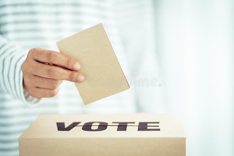 Insertion de papier de Brown dans la boîte de vote images stock
