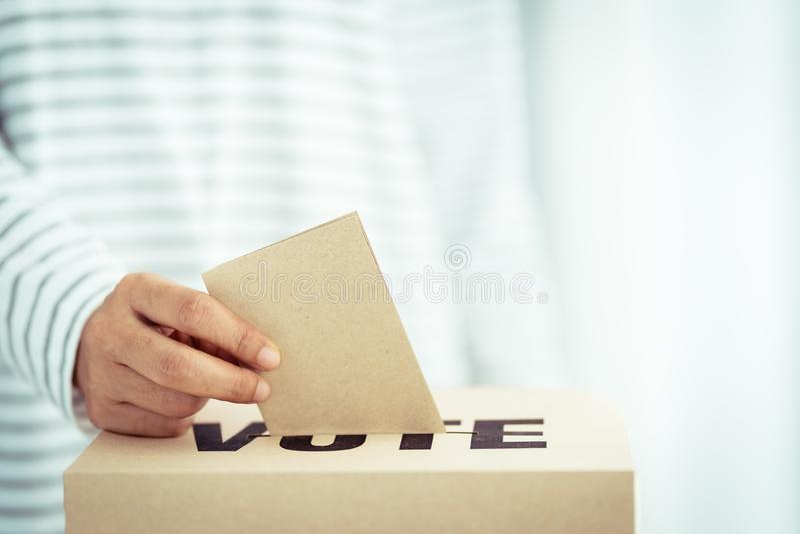 Insertion de papier de Brown dans la boîte de vote image libre de droits