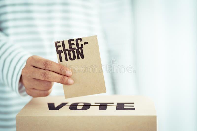 Insertion de papier de Brown dans la boîte de vote photographie stock