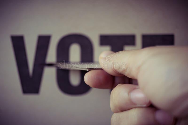 Insertion de papier de Brown dans la boîte de vote, concept de démocratie photos stock