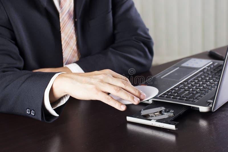 Inserzione del disco al computer portatile immagini stock