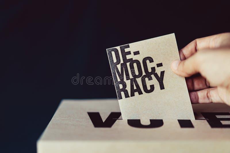Inserzione della carta di elezione in scatola di voto, concetto di democrazia fotografia stock