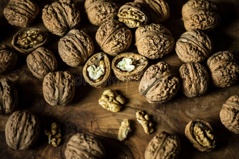 Walnuts on wooden table. Vegetarian food. Inshell nuts and peeled nuts. Healthy food for snacks and appetizers. Vegetarian food royalty free stock image