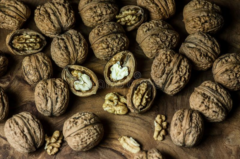 Walnuts on wooden table. Vegetarian food. Inshell nuts and peeled nuts. Healthy food for snacks and appetizers. Vegetarian food stock photography