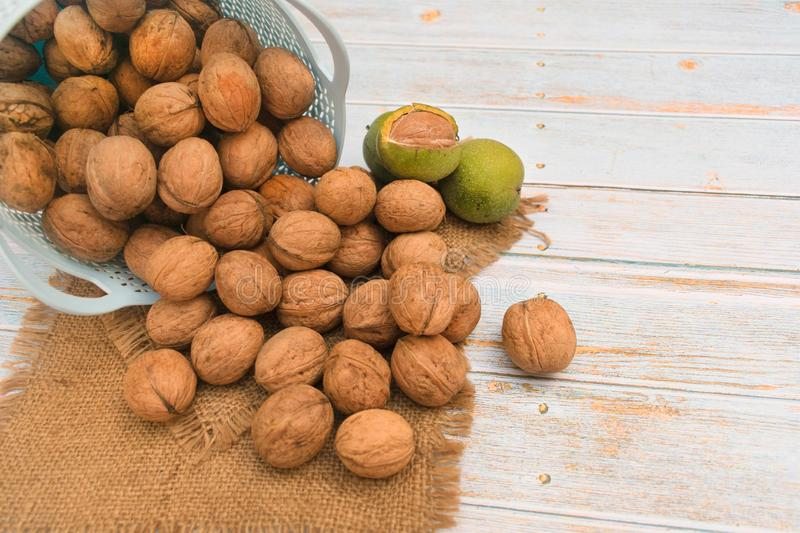 Inshell walnuts in a basket on a light wooden background. Inshell walnuts in a basket on a  wooden background royalty free stock image