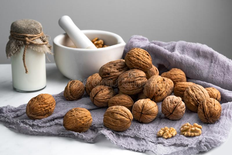 Inshell walnuts, a bottle of milk and a mortar with nuts, on a gray napkin, wooden background.  stock photo