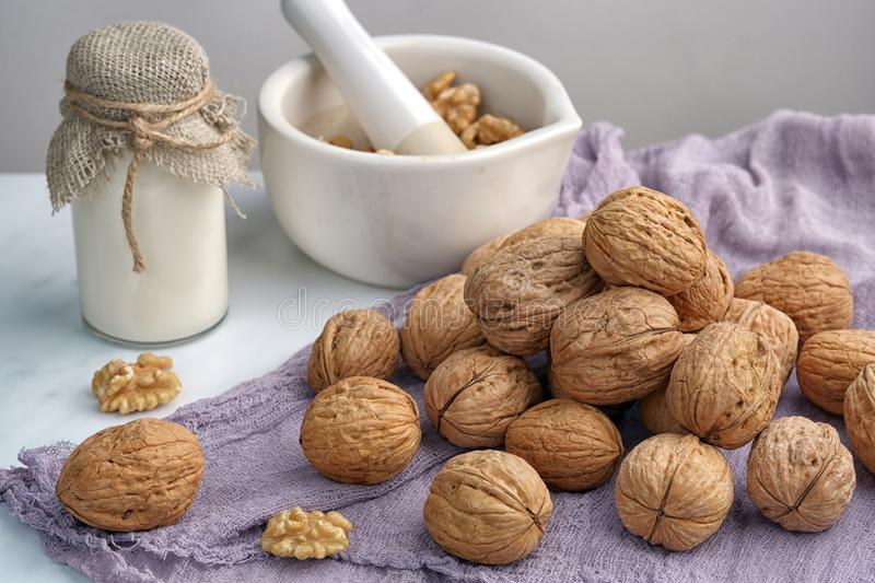 Inshell walnuts, a bottle of milk and a mortar with nuts, on a gray napkin, wooden background.  royalty free stock photography