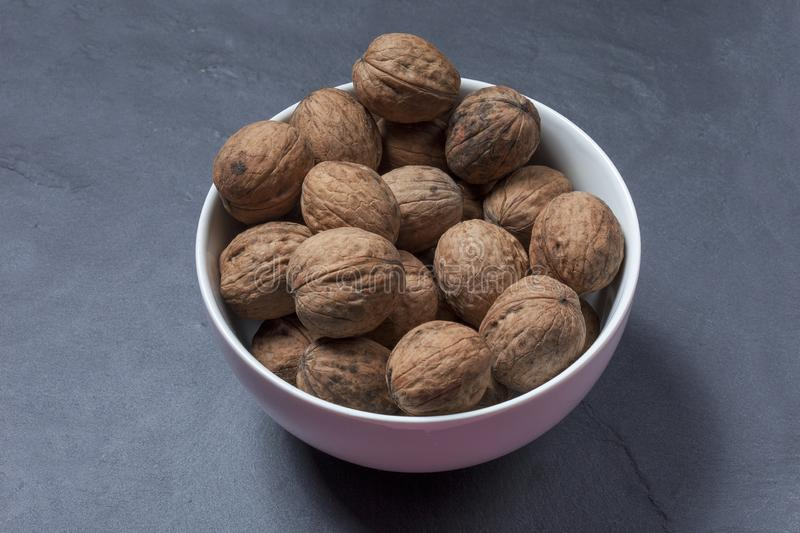 Inshell walnuts. In a plate on a dark background royalty free stock photo