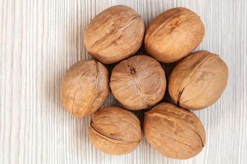 Inshell walnuts. On a wooden isolated background. Walnuts pattern stock photo