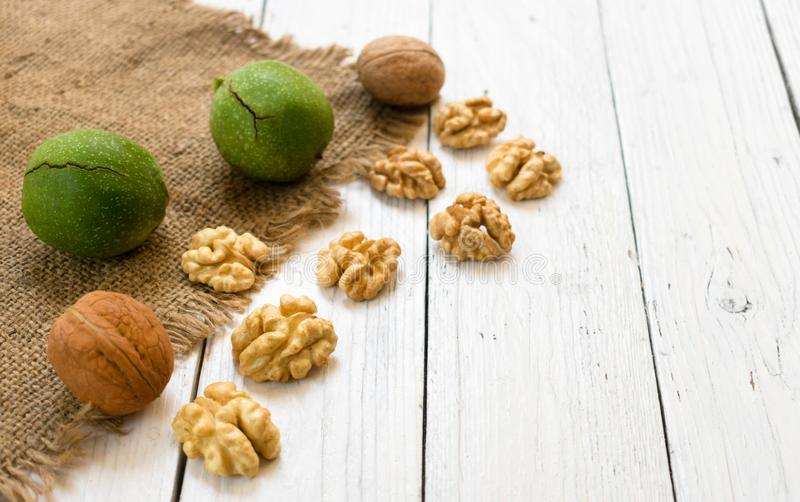 Inshell walnuts and walnut kernels on a white wooden table. The concept of a healthy diet. Inshell walnuts and walnut kernels on a wooden table. The concept of stock image