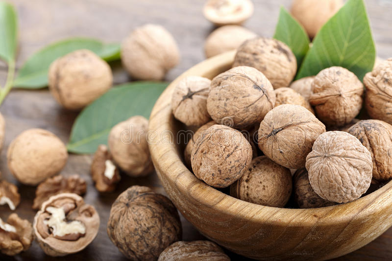 Inshell walnuts on a wooden background. Walnuts harvest with leaves, nutritious product, nuts in a plate and scattered on the table royalty free stock photos