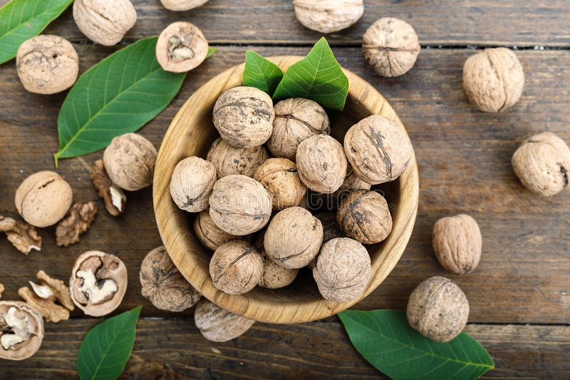 Inshell walnuts on a wooden background. Walnuts harvest with leaves, nutritious product, nuts in a plate and scattered on the table royalty free stock photography