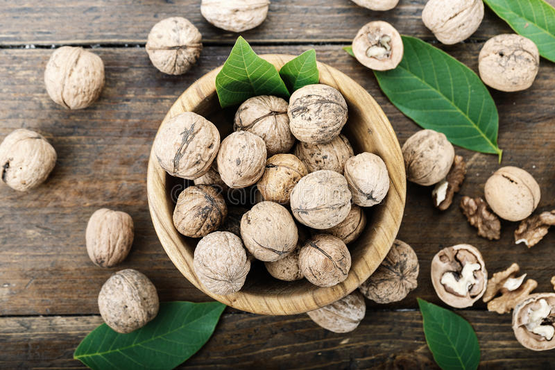 Inshell walnuts on a wooden background. Walnuts harvest with leaves, nutritious product, nuts in a plate and scattered on the table royalty free stock photo