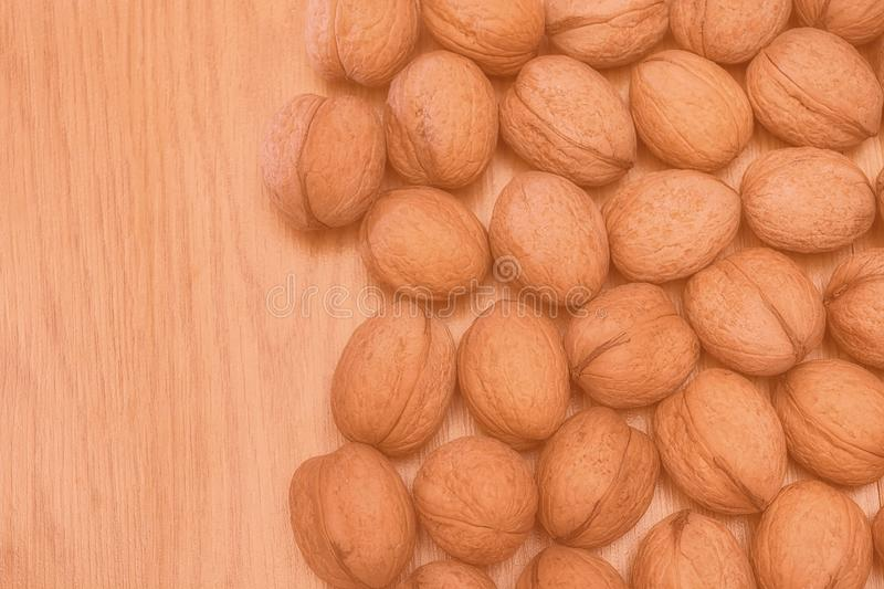 Inshell walnuts on a wooden table. Healthy food. Healthy lifestyle. Modern toned photo. stock photos