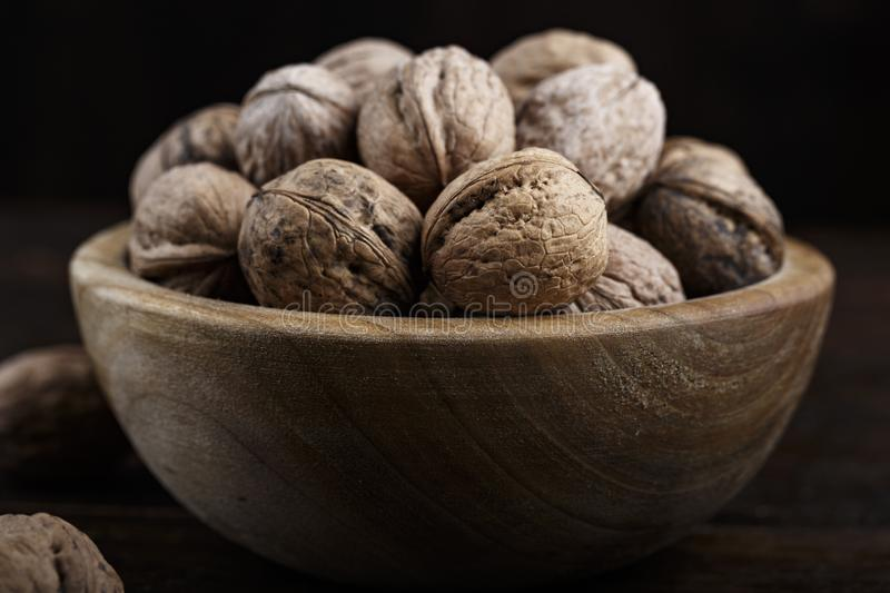 Inshell whole walnuts on dark wooden background. In a wooden plate stock photography