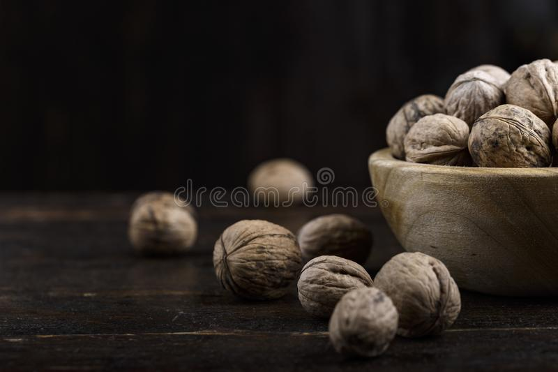 Inshell whole walnuts on dark wooden background. In a wooden plate stock images