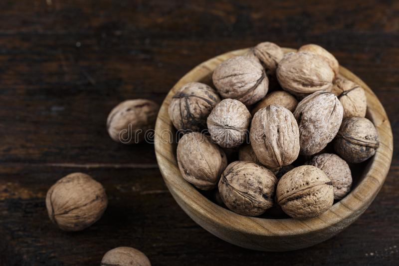 Inshell whole walnuts on dark wooden background. In a wooden plate royalty free stock image