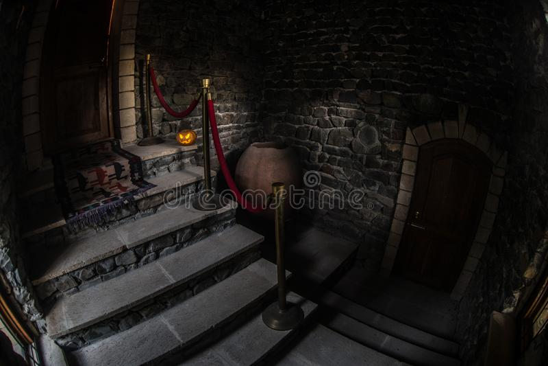 Insida av den gamla kusliga övergav herrgården Trappuppgång och kolonnad Allhelgonaaftonpumpa på mörk slotttrappa till källaren royaltyfri foto