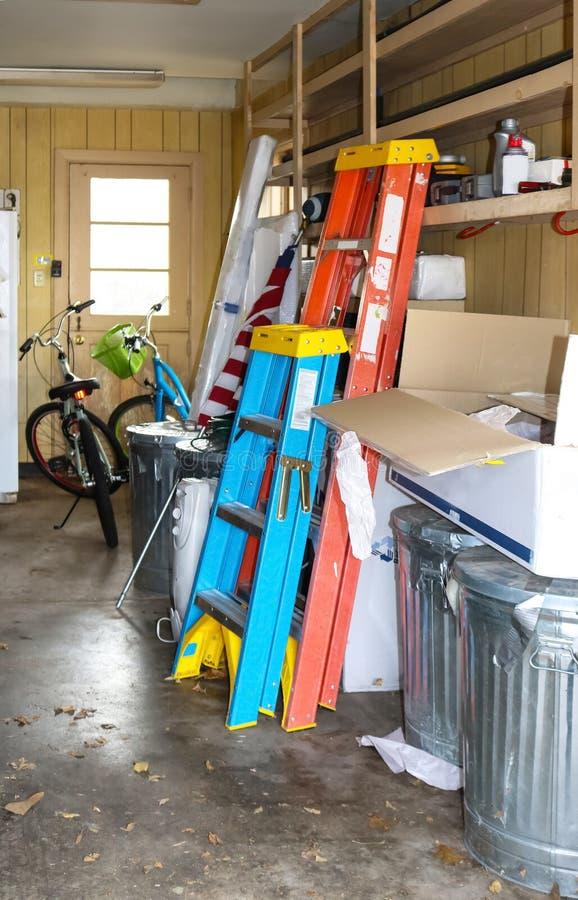 Insida av det smutsiga garaget med cyklar och stegar och amerikanska flaggan och askar och mer - selektiv fokus royaltyfria bilder