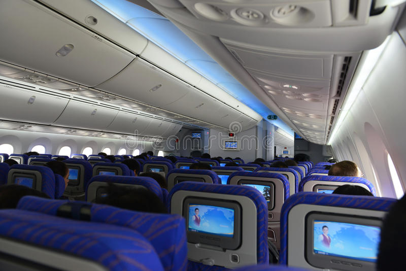 Inside Airplane Cabin with seats, passengers and baggage stock photo