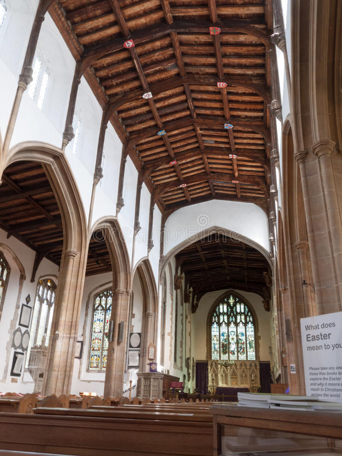 The Inside of a Beautiful Church in the Day Time. Day time church empty with wooden roof and pews, and an altar in the distance, plenty of high windows stock photo