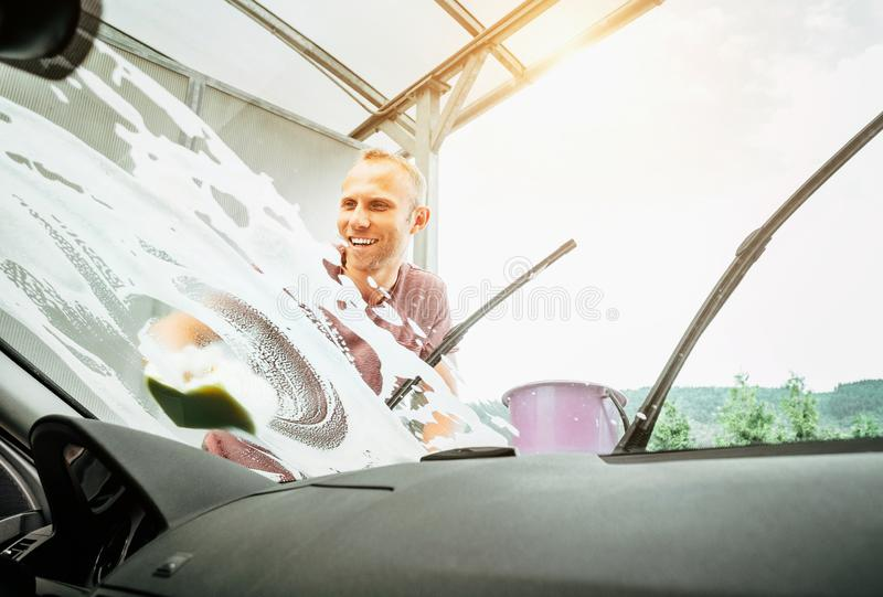 Inside the car camera view of Man washes his car windshield window royalty free stock photo