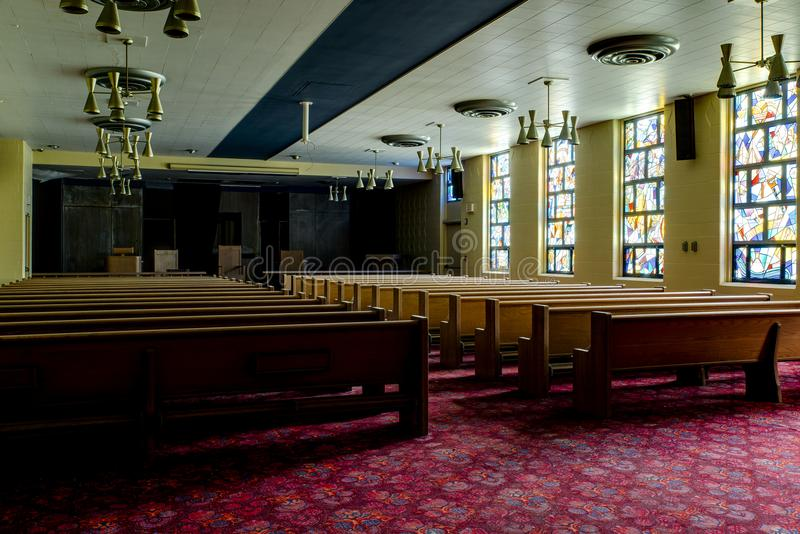 Derelict Chapel - Abandoned Veterans Hospital - Cleveland, Ohio. Inside a derelict chapel and church with golden oak pews in an abandoned Veterans Hospital near stock image