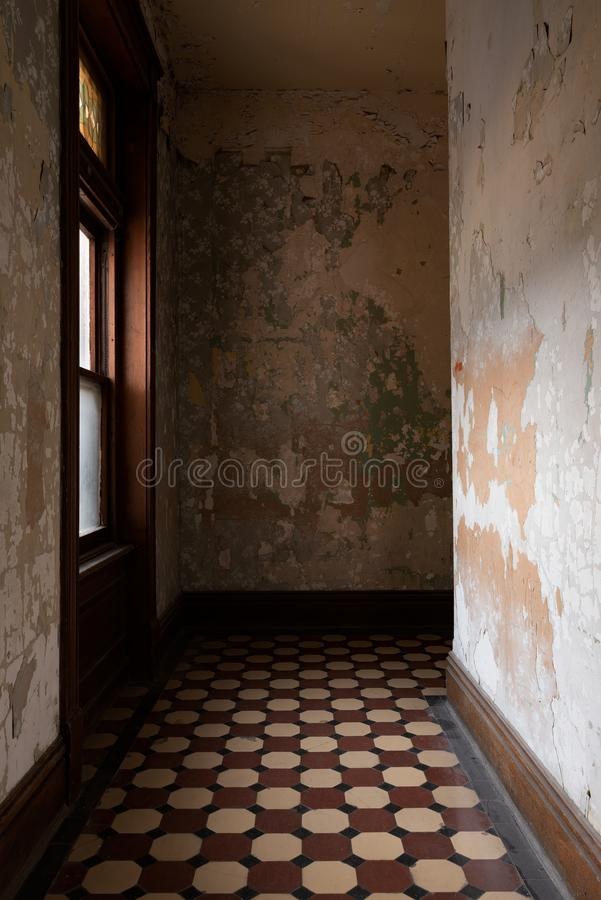 Derelict Hallway with Window - Ohio State Reformatory Prison - Mansfield, Ohio. Inside a derelict hallway with tile flooring, a window, and peeling paint at the stock image