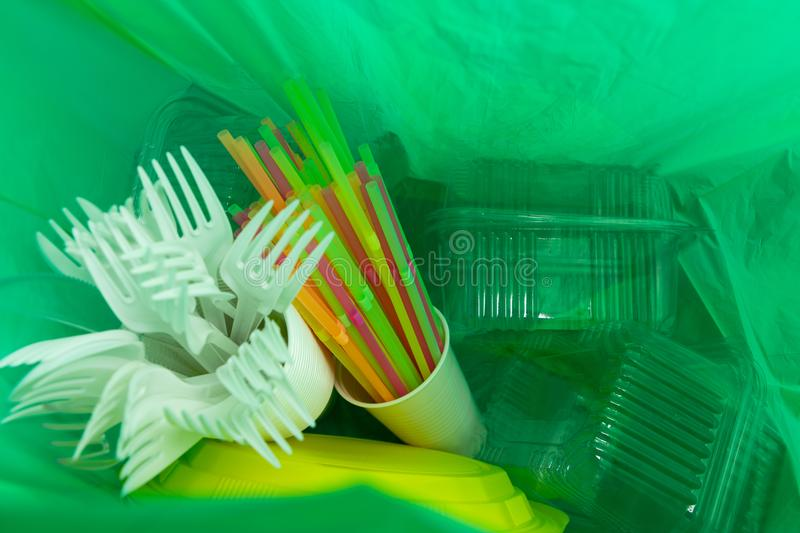 Inside of green plastic bag with single use cutlery and packages. Inside of green plastic bag with single use cutlery plates straws cup and package boxes as stock photography