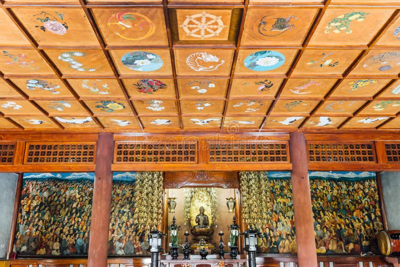 Inside Indosan Nippon Japanese Temple, Lord Buddha statue in the center with wall painted and wooden ceiling at Bodh Gaya. royalty free stock images