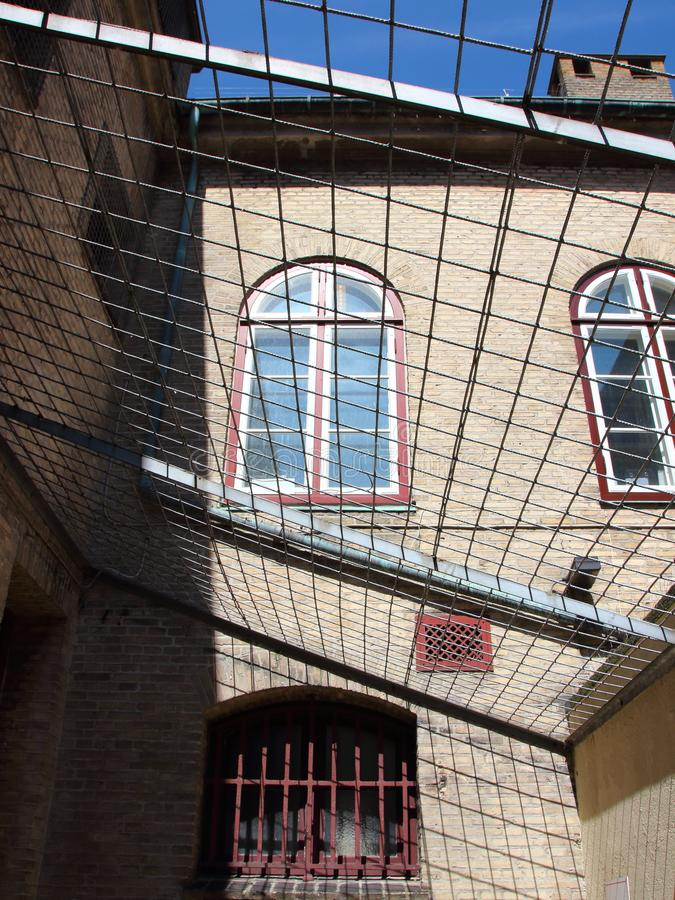 Inside of Jail Yard with Metal Grid Roof and Bars. Inside of Jail Yard with Metal Grid Roof and Red Bars royalty free stock photos