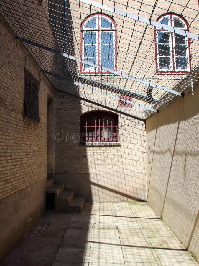 Inside of Jail Yard with Metal Grid Roof and Bars. Inside of Jail Yard with Metal Grid Roof and Red Bars stock photo