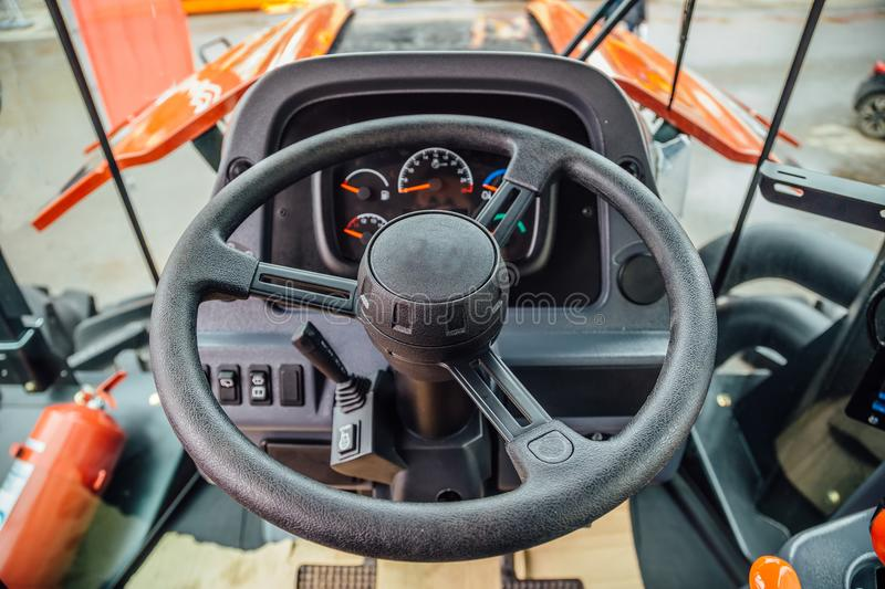 Inside modern agricultural tractor or harvester combine machine. Steering wheel. View from work place.  royalty free stock photo
