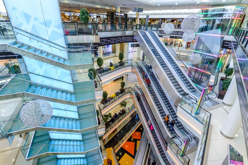 Inside the modern shopping center. Moscow - March 9, 2017: Interior of luxury mall, top view. Panorama of a large shop or store with stairs and escalators royalty free stock photos