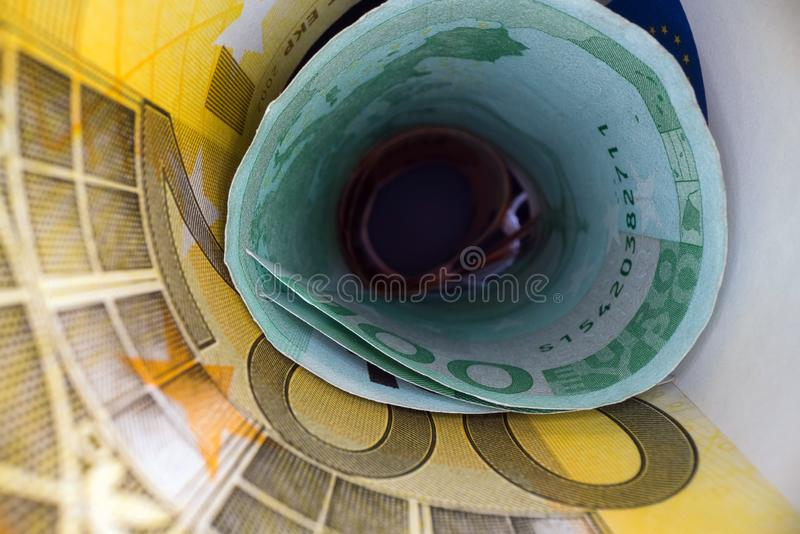 Inside the money tunnel. Abstract perspective view of euro back notes rolled in a tube. Saving and investing money royalty free stock photo