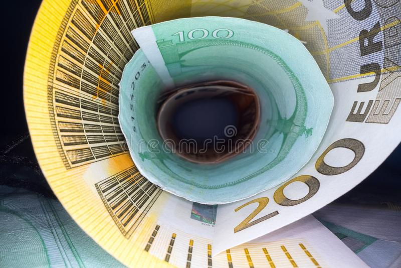 Inside the money tunnel. Abstract perspective view of euro back notes rolled in a tube. Saving and investing money royalty free stock images